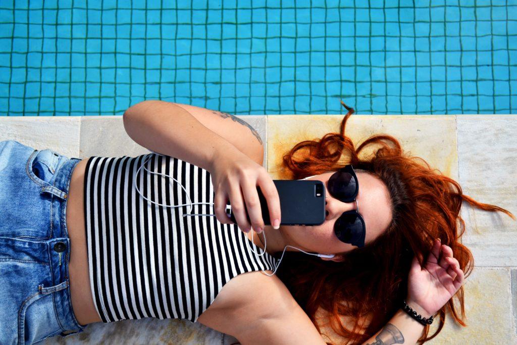 Jeune fille allongé au bord du piscine avec un téléphone à la main