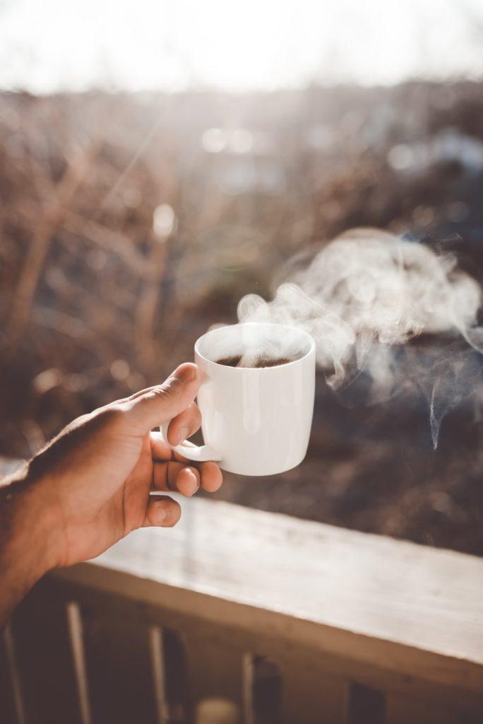 Tasse de café chaude dans une main